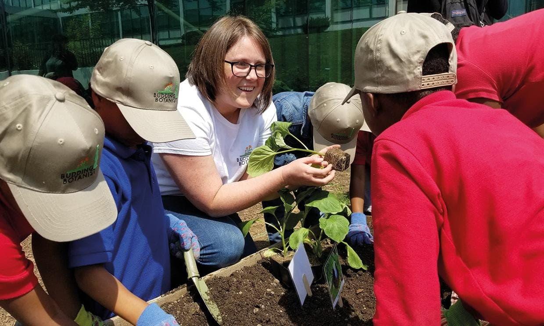Chidren gathered around smiling girl holding plant