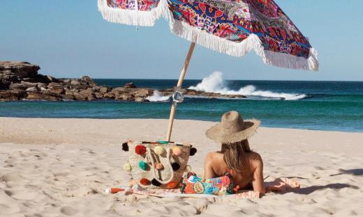 Woman in a hat on beach under colorful umbrella