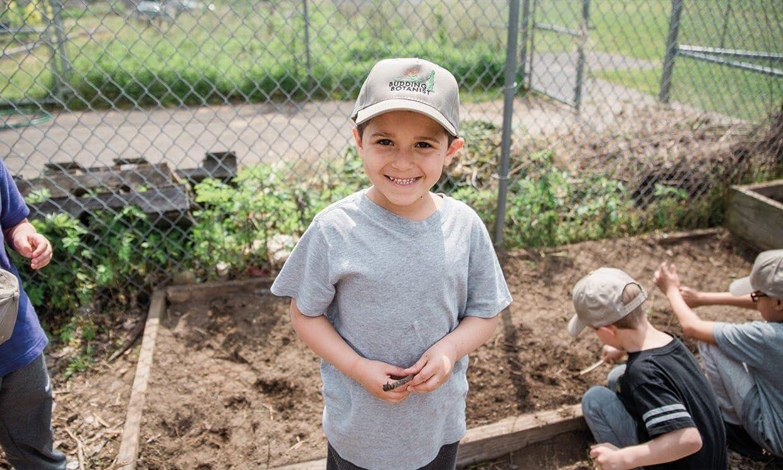 Boy smiling in front of garden