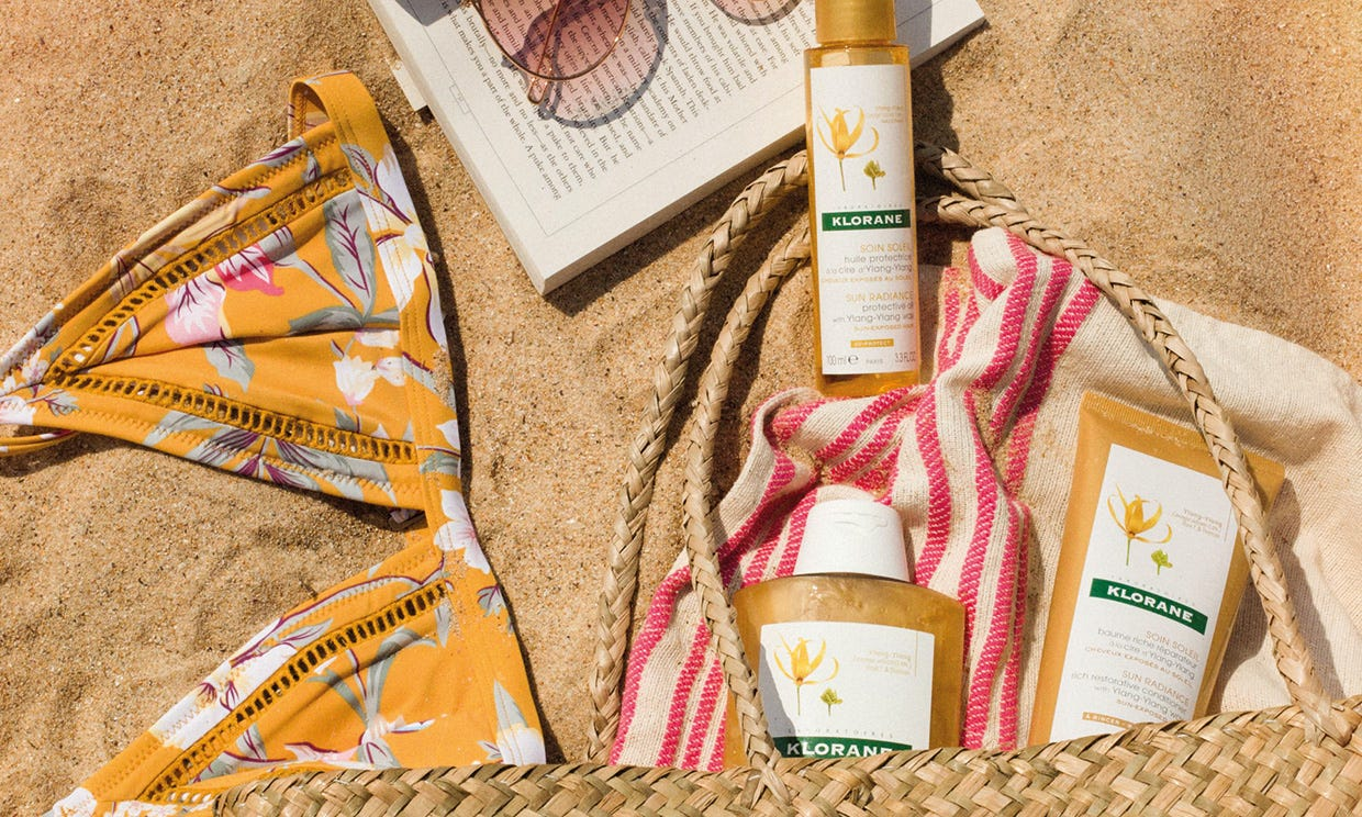 Ylang-Ylang collection in sand with bikini, beach bag, book and sunglasses